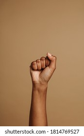 Fist held tightly against brown background. Close fist symbolizing the black lives matter movement.