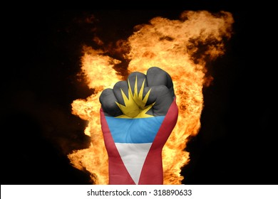 fist with the national flag of antigua and barbuda near the fire on a black background