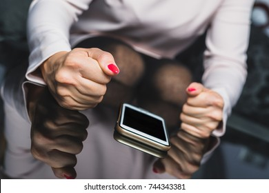 Fist in the phone. Anger on hand phone hits the phone. The feminine hand wants to hit his hand on the cell phone lying on the table. Bad message, not reply to messages, bad messages.
