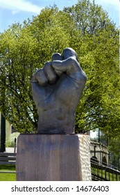 Fist sculpture is upraised towards the sky.  Tree in background and blue sky.
