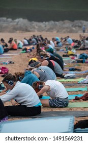 FISTRAL BEACH, CORNWALL, ENGLAND - AUGUST 24, 2019: Group of people taking part in a group session of silent disco yoga at sunset on the beach at Fistral Newquay, in Cornwall, UK. Editorial use only