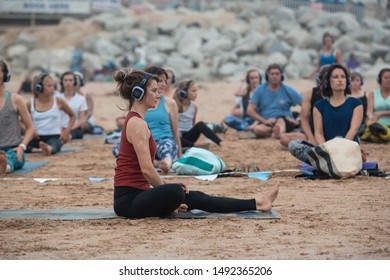 FISTRAL BEACH, CORNWALL, ENGLAND - AUGUST 24, 2019: Yogo instructor leading a group session of silent disco yoga at sunset on the beach at Fistral Newquay, in Cornwall, UK. Editorial use only