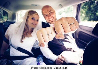 Fists of bride and groom with a new wedding rings. The newlyweds are located inside of their car on back seats. Faces with expressions of happiness in the background. (Focused on fists of newlyweds)