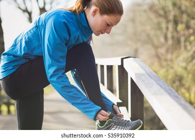 A fit and active woman tying her shoes before jogging in a park.