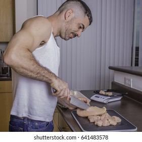 Fit, adult man prepping chicken breast on cutting board and food scale