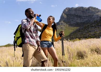 Fit afrcanicisches Paar mit Rucksäcken Nordic Walking mit Polen Trinkwasser in der Berglandschaft. gesunder Lebensstil, Bewegung in der Natur.