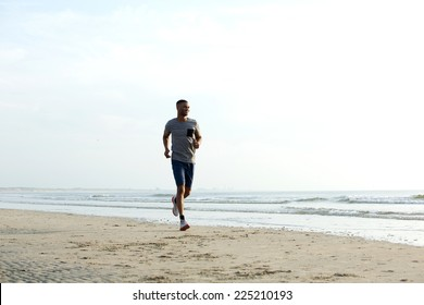 Fit african american man running alone at the beach