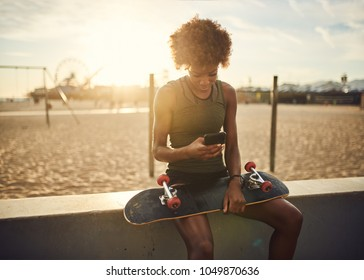 fit african american skater sitting down to look at smart phone at santa monica