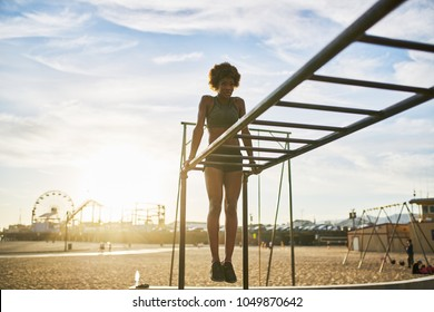 fit african american woman exercising on monkey bars