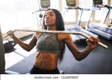 fit african american woman working out and stretching in gym