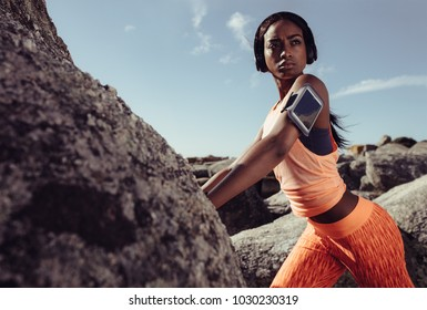Fit african woman standing by rock at the beach during workout session. Fitness woman in sportswear during training session outdoors.