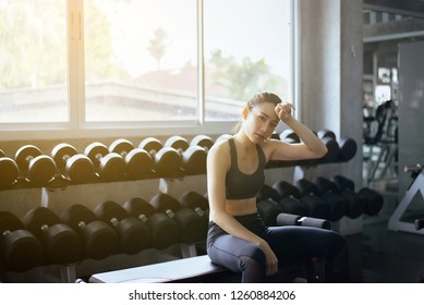 Fit asian beautiful woman sitting and relax after the training session in gym,Female taking a break after exercise and workout,Concept healthy and lifestyle