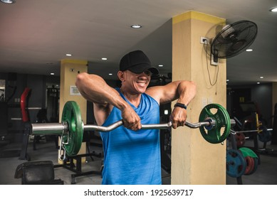 A fit asian guy does upright rows with an EZ curl bar at an open air gym. Traps upper back and shoulder exercise. Getting ready for summer.