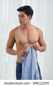 Fit Asian man standing with shirt in his hands