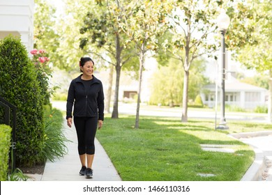 Fit Asian woman exercising and walking outside