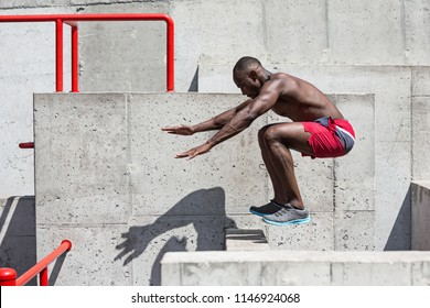 The fit athlete doing exercises at stadium. Afro or african american man outdoor at city. The jumping sport exercises. fitness, health, lifestyle concept