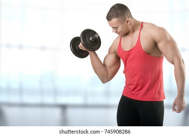 Fit athlete doing standing dumbbell curls for training his biceps, in a blue background