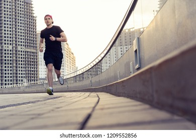 Fit athlete running outdoors to stay healthy. Sporty Young Man Running