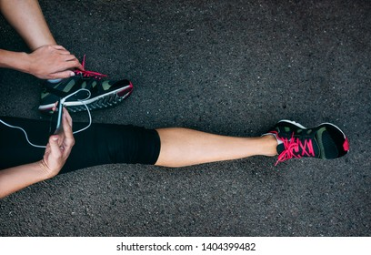 Fit athlete woman runner in sportswear relaxing after training with smartphone. Top view of female lags in sport shoes and outfit on city trail road. Workout lifestyle.