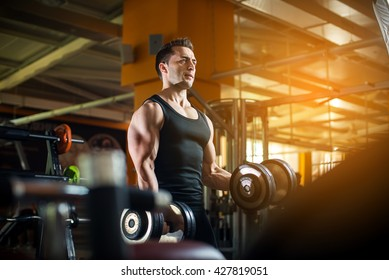 Fit Athlete Working Out Biceps at the gym.