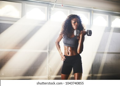 fit athletic african american woman lifting weights inside home gym in garage