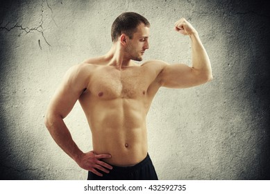Fit athletic bare-chested man in black pants is showing biceps on his left arm isolated on cracked concrete wall background