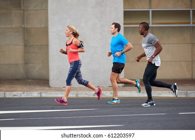 Fit athletic group of people running exercising together through urban landscape cityscapes
