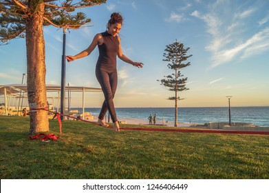 Fit, athletic, latin young girl balancing on slackline at the beach in Perth, Australia, in a sunny day.  Perth, WA, Australia 27/05/2017