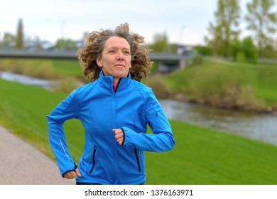 Fit athletic middle-aged woman jogging on a road alongside a canal approaching the camera with a smile of pleasure in a healthy lifestyle concept
