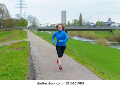 Fit athletic middle-aged woman jogging on a road alongside a canal approaching the camera. Front full-length portrait with copy space