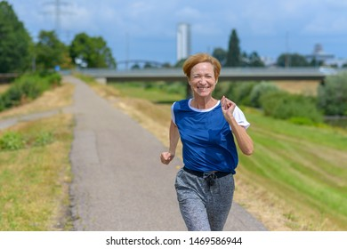 Fit athletic middle-aged woman out jogging along a rural road smiling as she approaches the camera