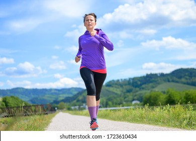 Fit athletic middle-aged woman out jogging through fresh green spring countryside in a low angle view in a healthy lifestyle concept