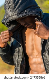 Fit, athletic and muscular African black male wearing black bomber jacket hoodie with zipper, isolated with blue sky