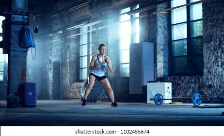 Fit Athletic Woman Does Footwork Running Drill in a Deserted Factory Remodeled into Gym. Cross Fitness Exercise/ Workout Aimed at Strengthening Legs, Enhancing Her Agility and Speed. Cold Ambient.