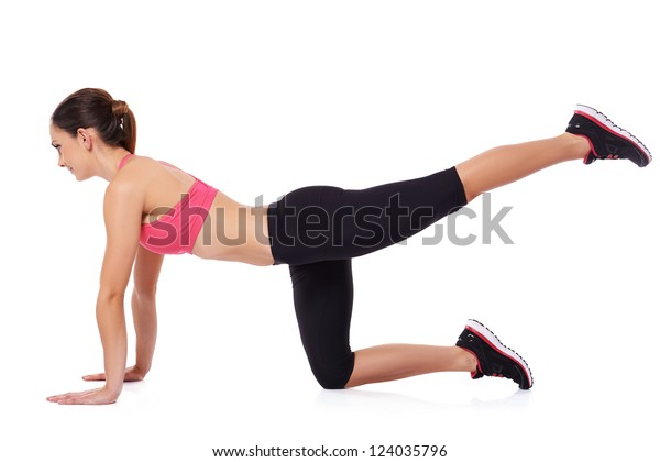 Fit athletic woman exercising in a studio down on the floor balancing on her arms and one knee with the other leg raised up behind her in the air