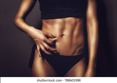 Fit athletic woman pinching her stomach skin showing perfectly shaped abs and body with no cellulite