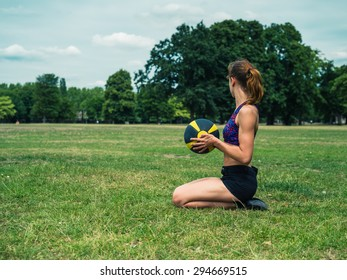 A fit and athletic young woman is sitting on the grass in a park and holding a medicine ball