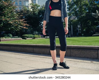 A fit and athletic young woman with toned abs is standing in a city park on a sunny day