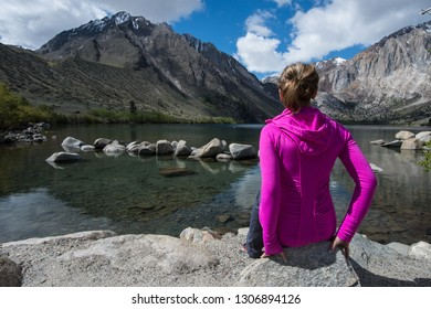 Fit attractive female sits alone by Convict Lake in the springtime, located off of US-395, near Mammoth Lakes California in the eastern Sierra Nevada mountains, Inyo National Forest.
