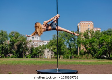 Fit attractive girl dancing near portable pole at summer day on the field