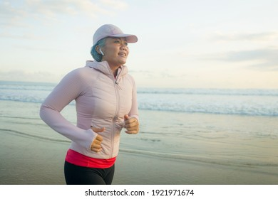 fit and attractive mature woman with grey hair doing beach workout on her 50s running on the beach happy and free in senior fitness selfcare and wellness concept