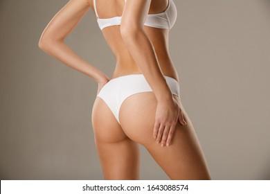 Fit attraktive Frau, die ihre Haut auf Hüften zu kleben, Testen subkutane Körperfettschicht. Unwiderruflicher, flimmernder Körper - Beispiel für Sport, Diät, Fitness oder plastische Chirurgie und ästhetische Kosmetologie