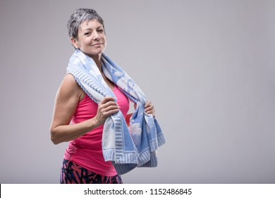Fit attractive woman with a towel around her neck after working out in a gym smiling at the camera in a health and fitness concept