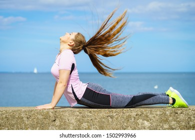 Fit attractive young woman wearing fashionable outfit working out being active outside. Practice yoga next to sea, having windblown hair.