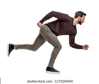A fit bearded man in casual sweater stands in a low running position with only one foot on the ground. Running fast. In time for everything. High speed life.