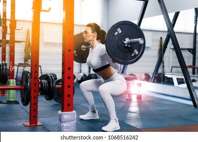 Fit beautiful girl doing squats with barbell in gym. The development of leg muscles, strengthening of the spine after injuries