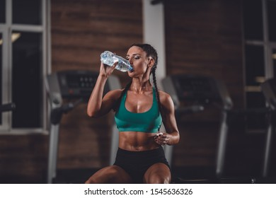 Fit and beautiful girl rest after training and drink water.