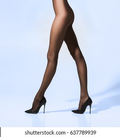 Fit and beautiful legs in sexy pantyhose. Woman in hosiery over cyan background.