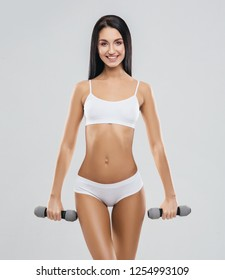 Fit and beautiful woman in swimsuit. Sporty girl with dumbbells. Fitness, diet and healthy lifestyle concept.