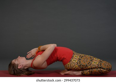 Fit beautiful young healthy sporty woman exercising yoga on grey paper background at photo studio.